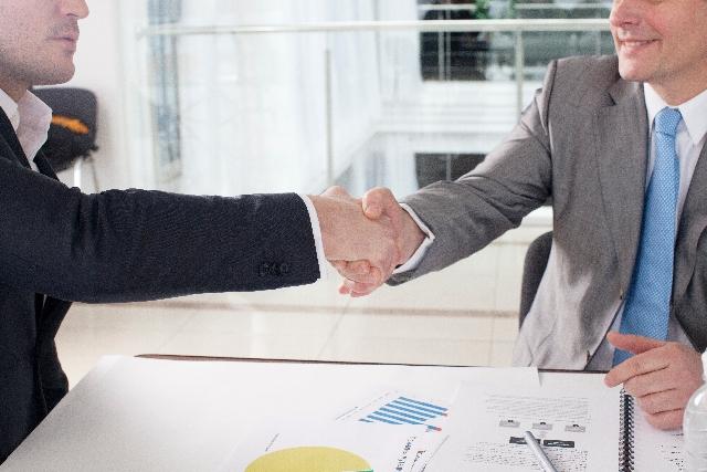 スーツ姿の男性2人が笑顔で握手している写真
